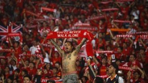 Indonesian Liverpool supporters hold scarves during a friendly soccer match between Liverpool FC and the Indonesian national team in Jakarta