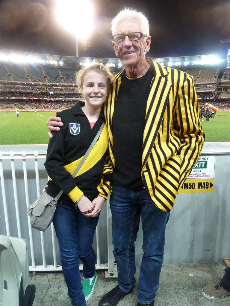 Tiger love under Friday night lights: Doug Sinclair, 66, from Wattle Glen, all smiles at quarter time in his yellow-and-black candy striped suit, with 12-year-old grand daughter, Lily.